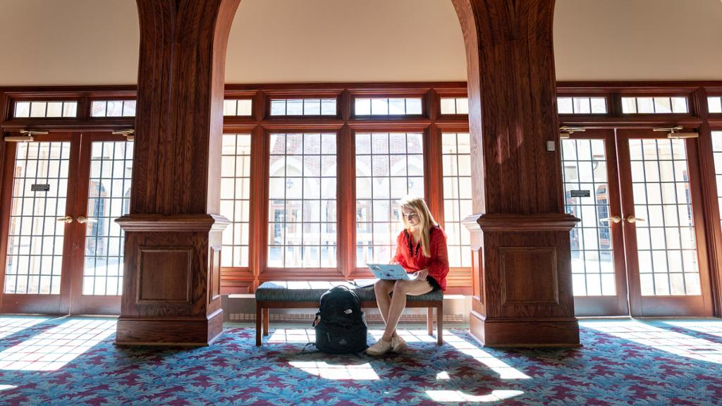 A female student works from her laptop on a bench in the Modlin Center for the Arts