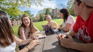 Students socialize around a picnic table on the Westhampton Green