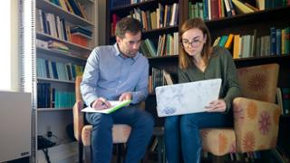 A female student using a laptop has a discussion with a male faculty member in front of a colorful bookcase