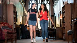 Two female students walking together in a study space
