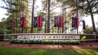 Red and blue University of Richmond banners hang over the brick wall that serves as the entrance to campus