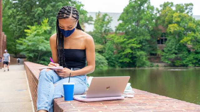 Female student wearing a mask studies next to Westhampton Lake