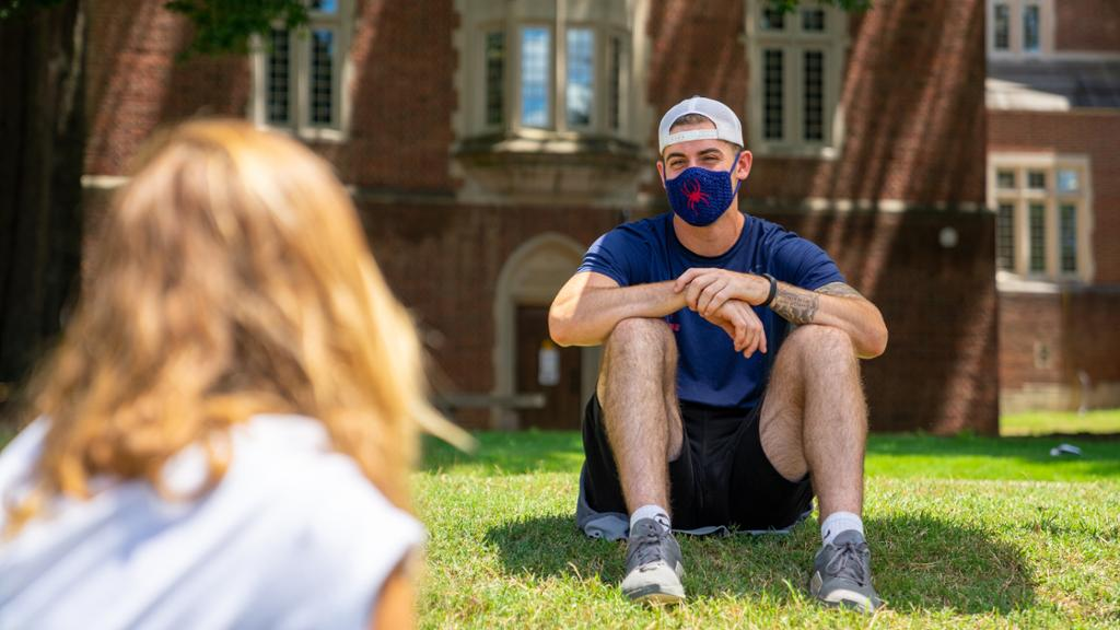 Students wearing masks have a conversation outdoors in front of Boatwright Library