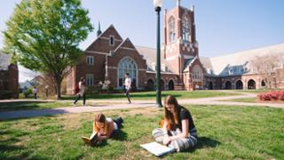 Students reading and studying on the grass in front of Jepson Hall
