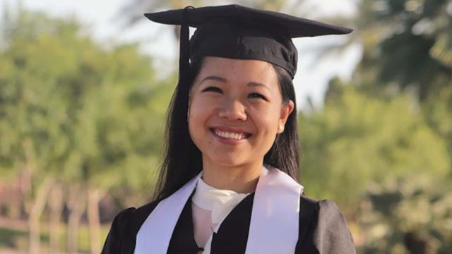 Anna Cheng smiling in her graduation regalia.