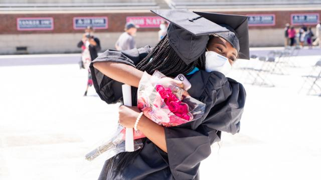 Students hug at graduation