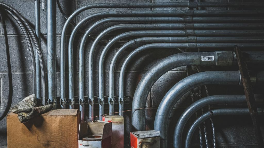 A cropped view of industrial metal piping from the steam plant building