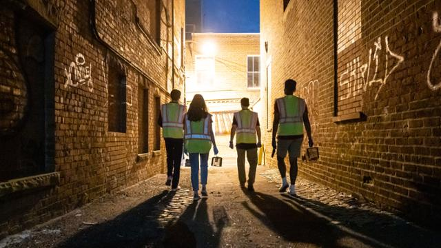 Professor Jonathan Richardson and three students walking down an alley at night in downtown Richmond, holding traps to catch rats for research.