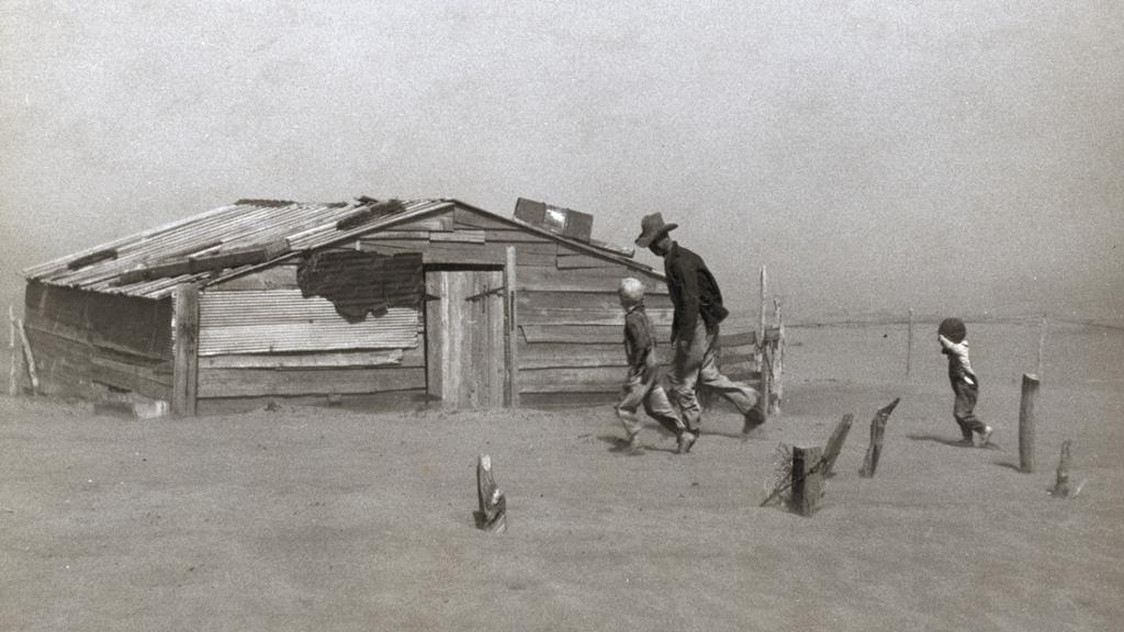 Farmer and sons walking in the face of a dust storm in Oklahoma. Photograph by Arthur Rothstein