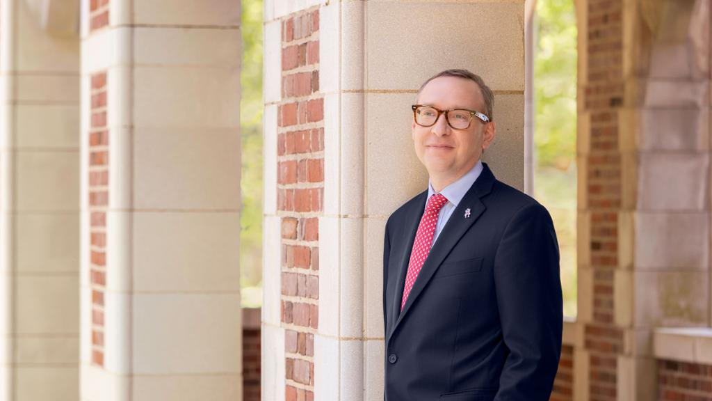 Incoming University of Richmond president Kevin Hallock, standing in front of a building on campus.