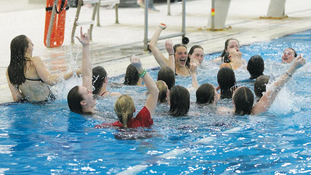 The Spider women's swim team celebrates their A-10 championship victory in the pool
