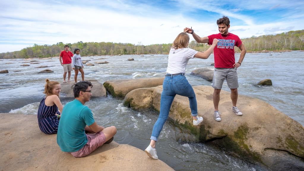 A male student helps a female student cross over large rocks in the James River while other students sit on rocks nearby.