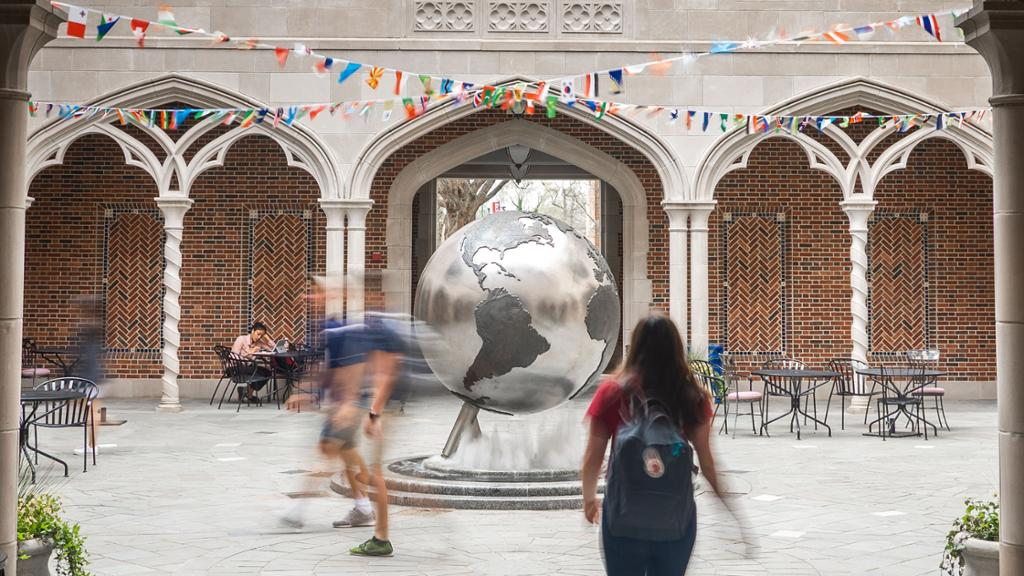 Students walk through the courtyard of the International Center, which features a large globe in the center.
