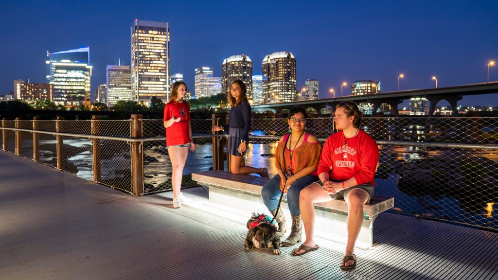 Students hanging out on a bridge in front of the Richmond skyline