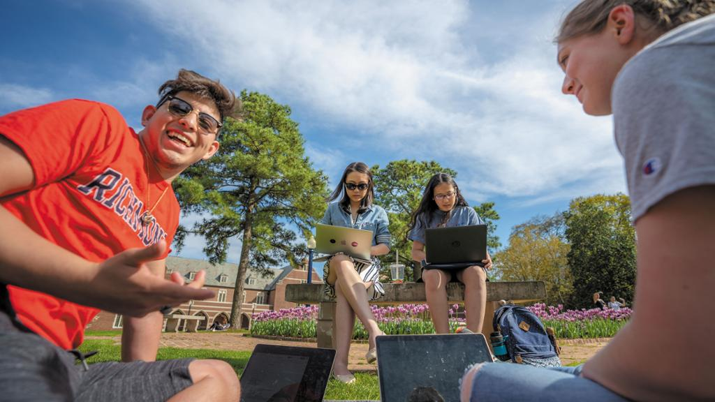 Four students sit together outside with laptops.
