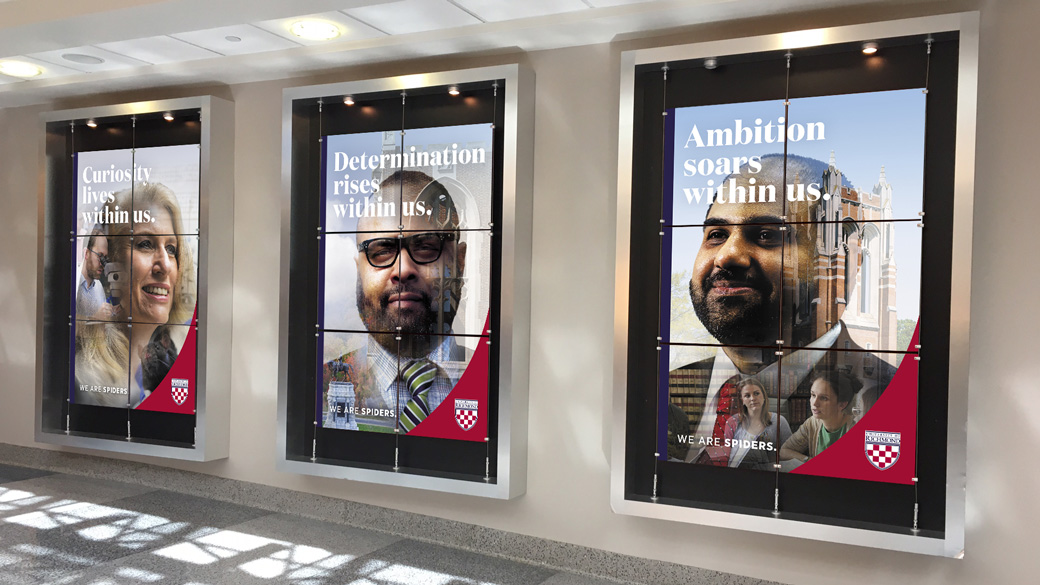 Three large advertisements at the Richmond airport featuring portraits of three faculty members.