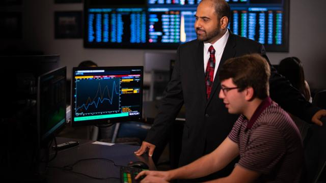 student and professor working in Richmond's finance trading floor