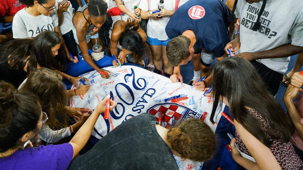 Members of the Class of 2020 sign their class banner with red and blue markers.