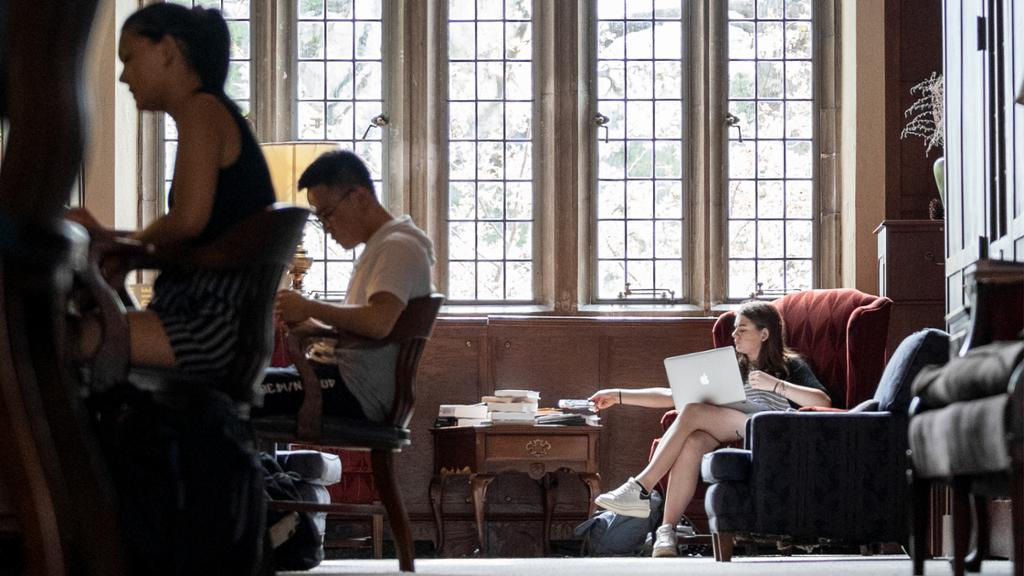Three students, who appear to be studying, in Ryland Hall. There is a large Gothic window behind one student sitting in a chair with a laptop.