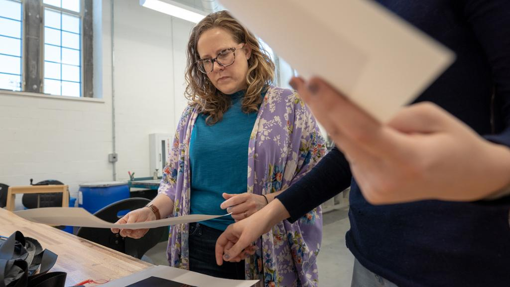 Faculty member working with a student in a printmaking class.