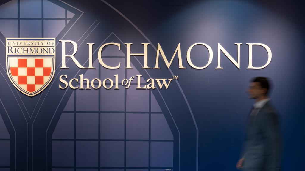Student walking in front of a blue wall in the law school. The Richmond Law School is logo is on the blue wall behind him.