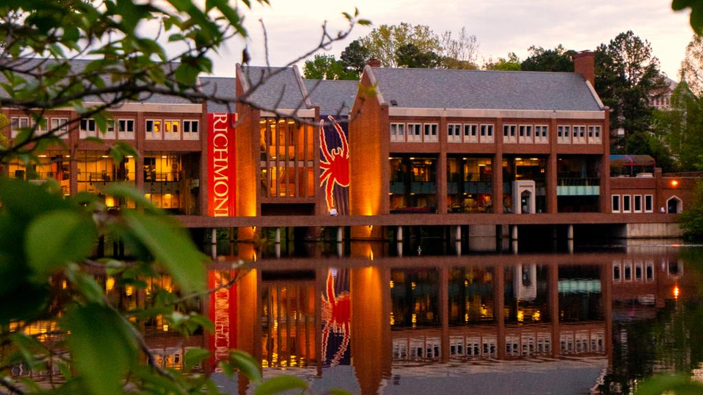 Tyler Haynes Commons at sunset. The large red and blue Spider banners hanging from the building are reflected on the surface of the lake.