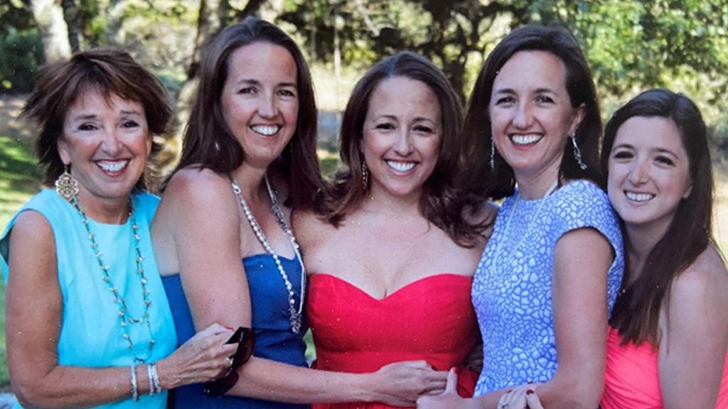 Terry Sylvester and her daughters Natalie, Whitney, Hilary, and Carly wear bright colors and stand arm-in-arm, smiling at the camera