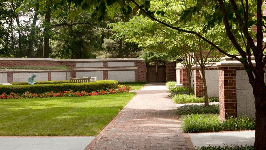a view of the columbarium in the spring, featuring the donor recognition walls and a fountain