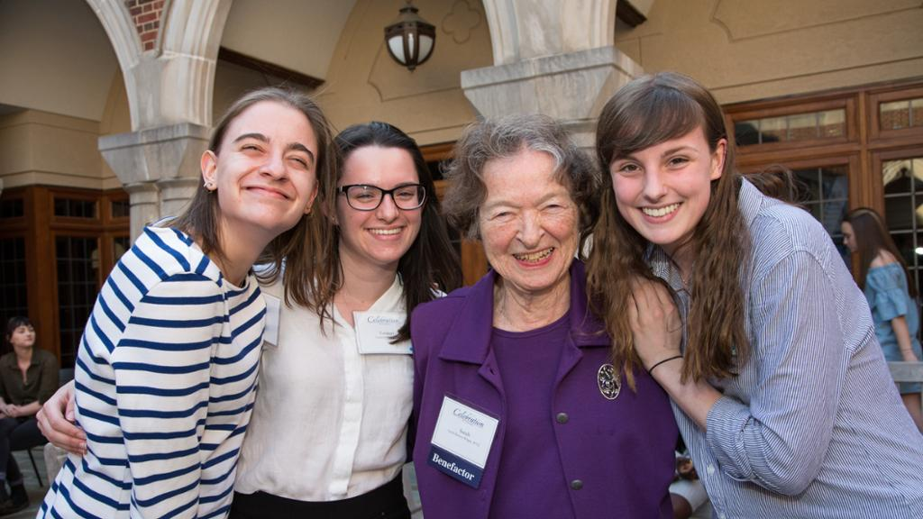 A donor poses with three students, all are smiling with their arms around one another