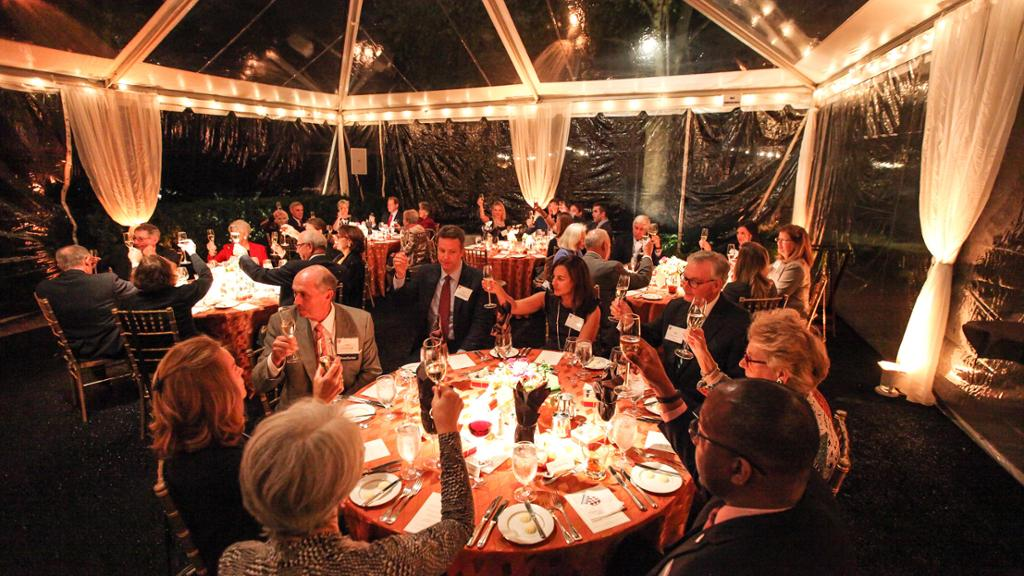 donors sit at round tables in candlelight and raise their glasses in celebration