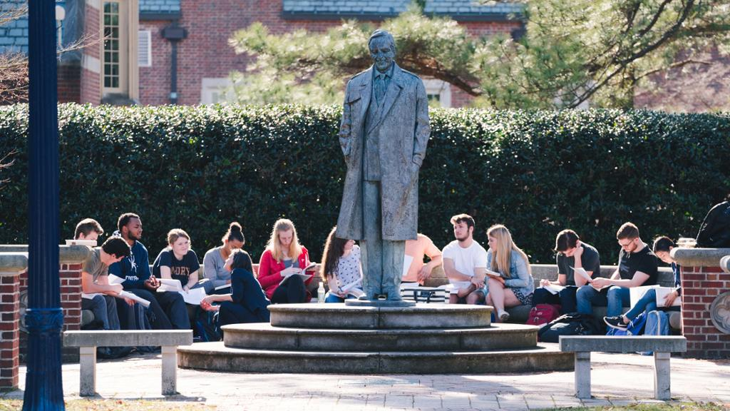 Students participating in a class outdoors around the Robins statue.