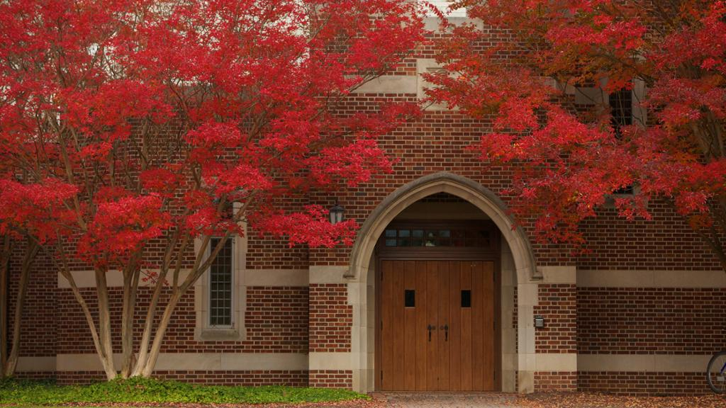 Door to Jepson Hall framed in trees with red fall leaves.