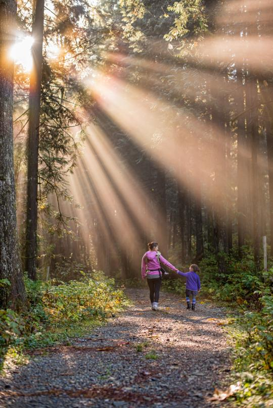 mother and daughter walking in the woods