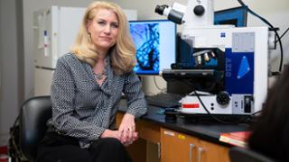 Kelly Lambert in front of microscope