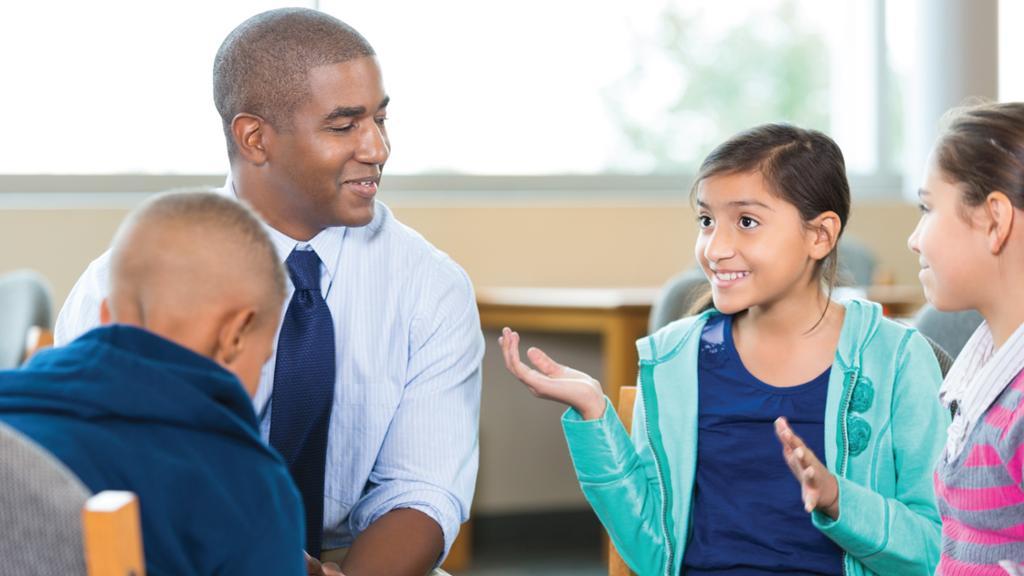 Teacher teaching students around table