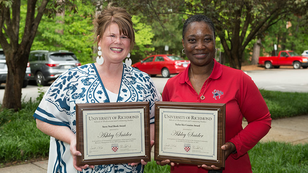 Ashley Snider receiving award plaques from Dean Wilson