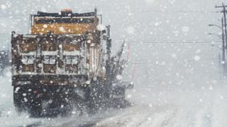 Snowplow plowing snow-covered road with heavy snow falling