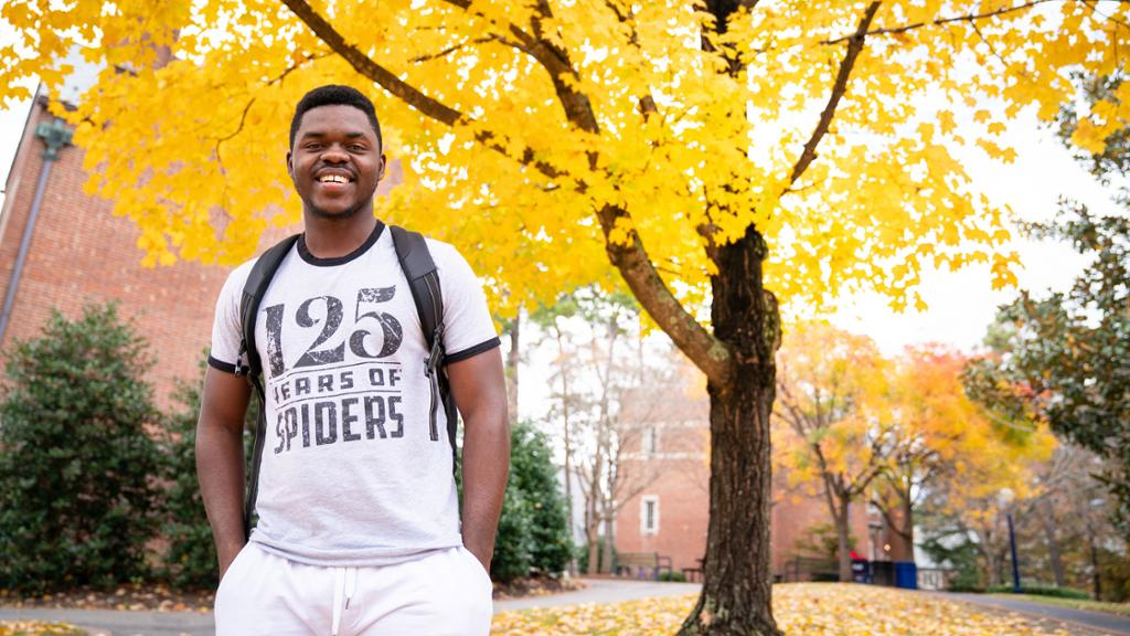 Student smiling in front of a tree.