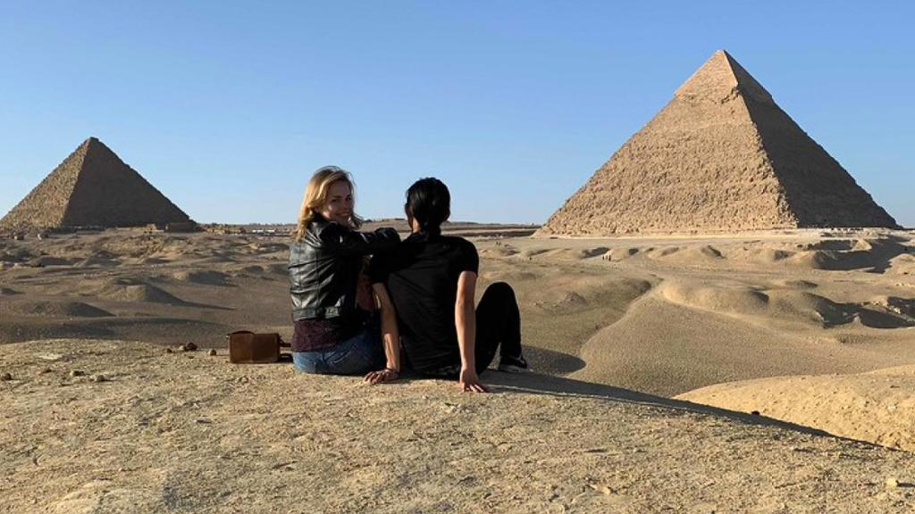 Two students sitting on the sand in Egypt in front of the pyramids.