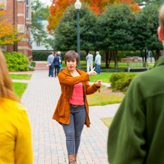Student providing a campus tour to a group of prospective students.