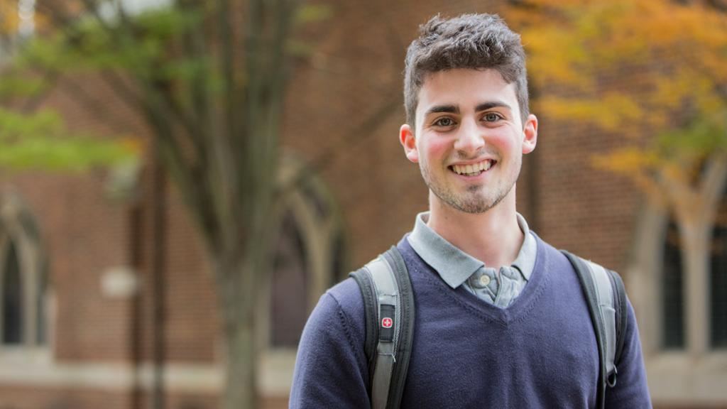 Close-up of a smiling student standing outside of a brick campus building.