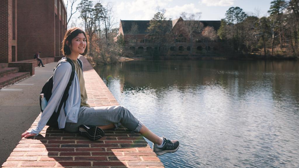 Student sitting outside of Tyler Haynes Commons next to Westhampton Lake.
