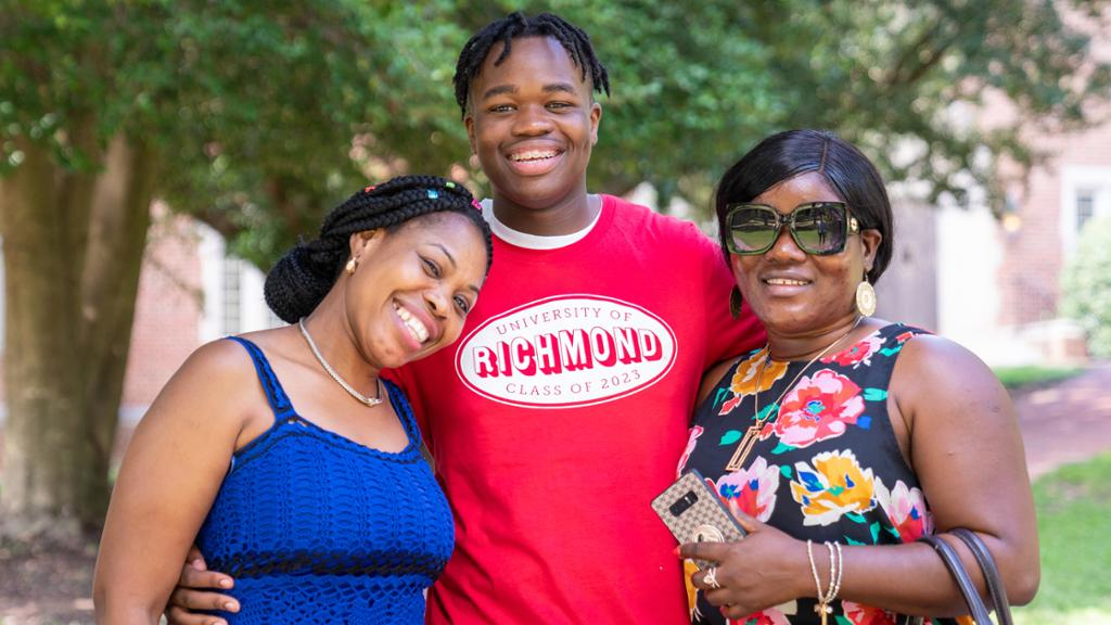 Student hugging two of his family members outside of a dorm on move-in day.