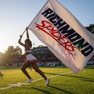 University of Richmond cheerleader waving a Richmond Spiders flag while running down the football field.