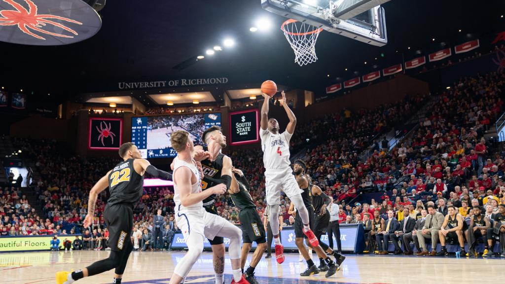 Richmond basketball players compete against VCU in the Robins Center in front of fans.