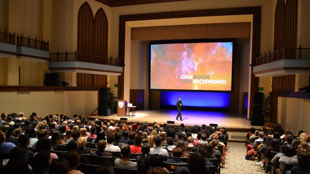 A lecturer stands at the front of a full auditorium with a screen behind her that says One Book, One Richmond.