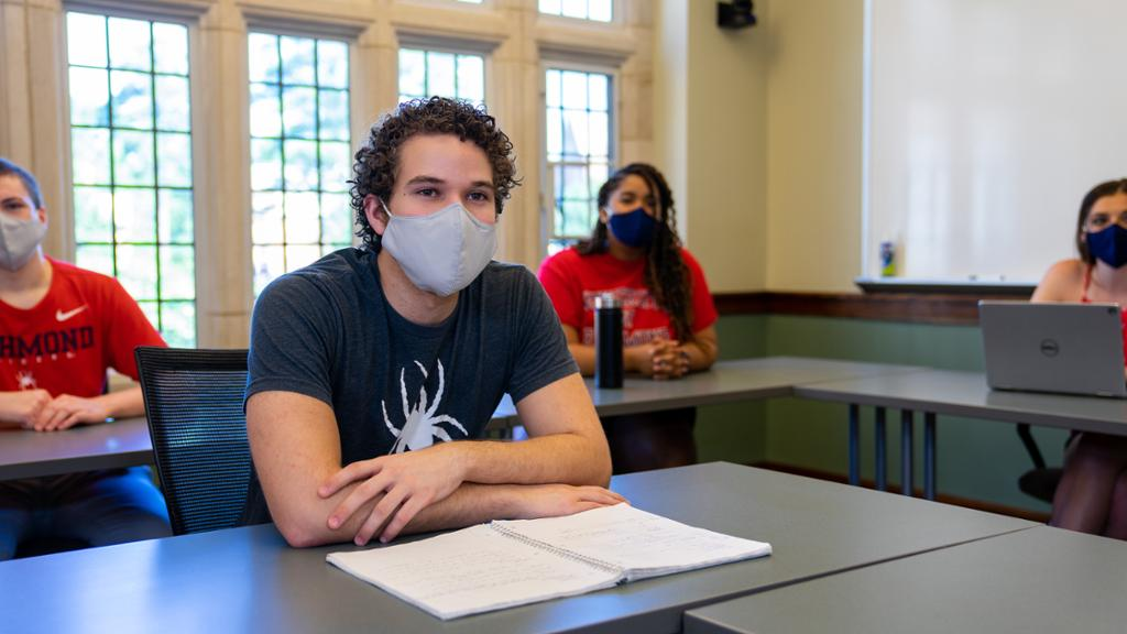 Four students sitting spaced apart in a classroom wearing face coverings.