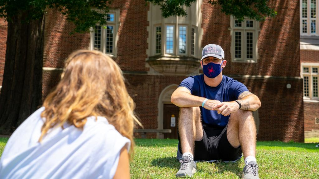 Two students sit facing each other on the lawn outside the library. The student facing the camera is wearing a face covering.