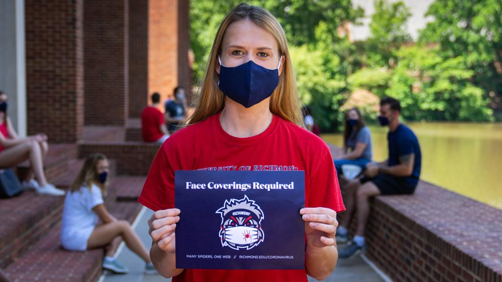 Student holding face coverings required sign