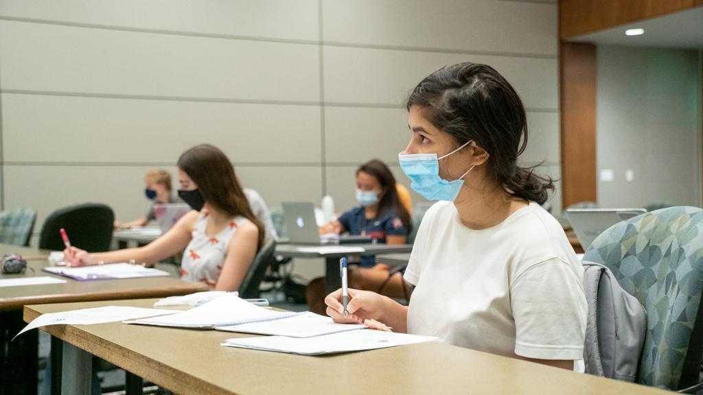 A student wearing a face covering takes notes during a class.